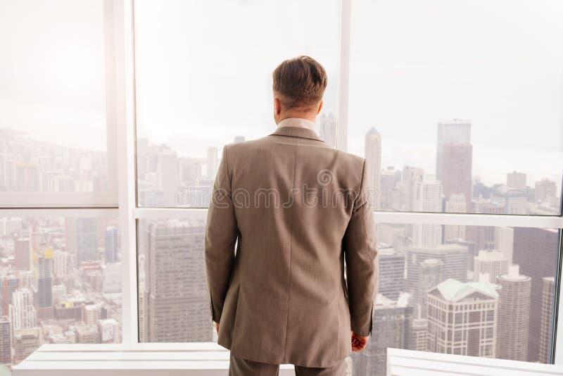 Tylni widok stoi blisko okno biznesmen zdjęcia royalty free