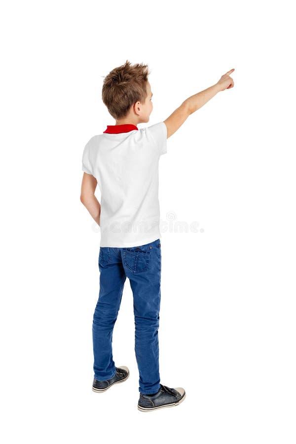 Tylni widok szkolna chłopiec wskazuje upwards nad białym tłem zdjęcie royalty free