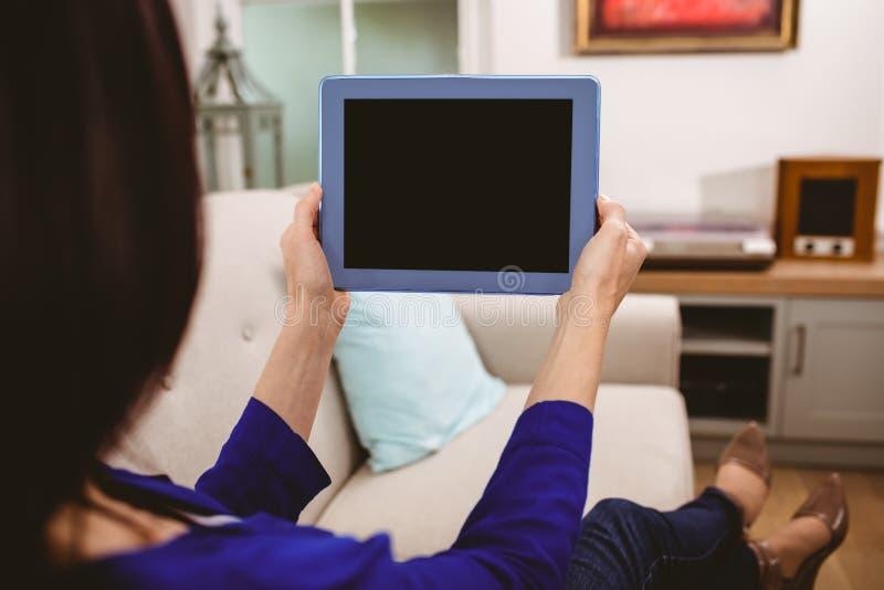 Tylni widok trzyma cyfrową pastylkę kobieta obraz royalty free