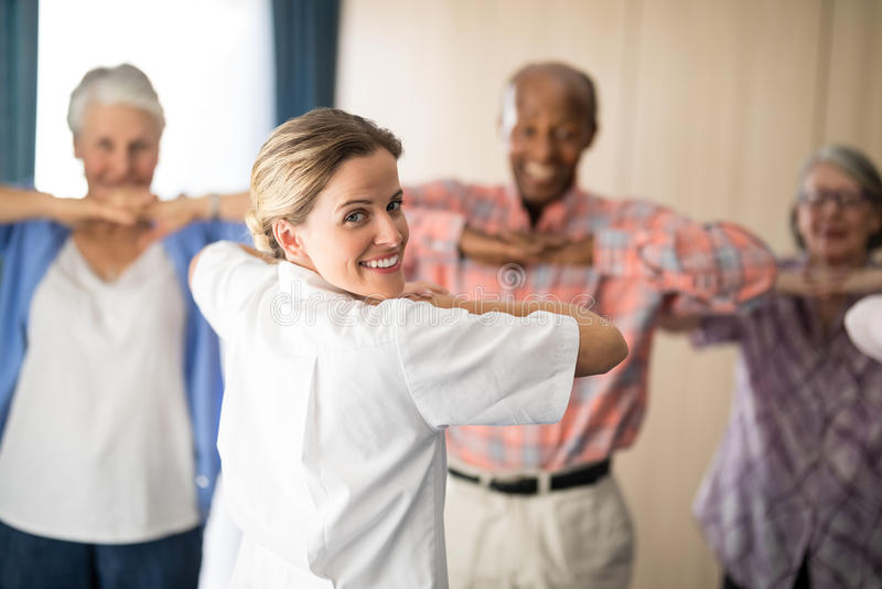 Tylni widok uśmiechniętej kobiety doktorski ćwiczyć z starszymi ludźmi zdjęcia royalty free