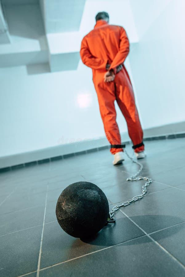 tylni widok więzień w pomarańcze mundurze z ciężarem pętającym obraz stock