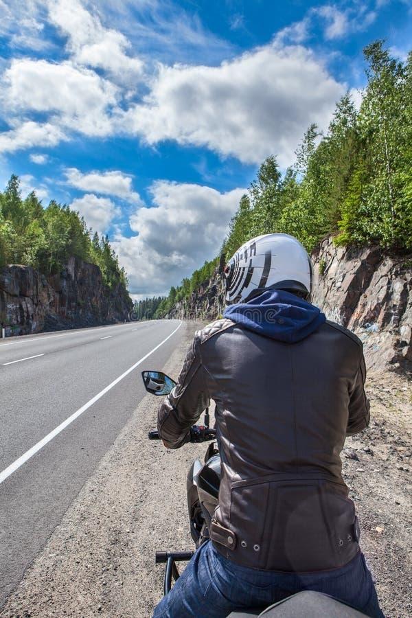 Tylni widok zatrzymujący na poboczu motorbiker Siedzieć na motocyklu w rzemiennym stroju i białym hełmie zdjęcie royalty free