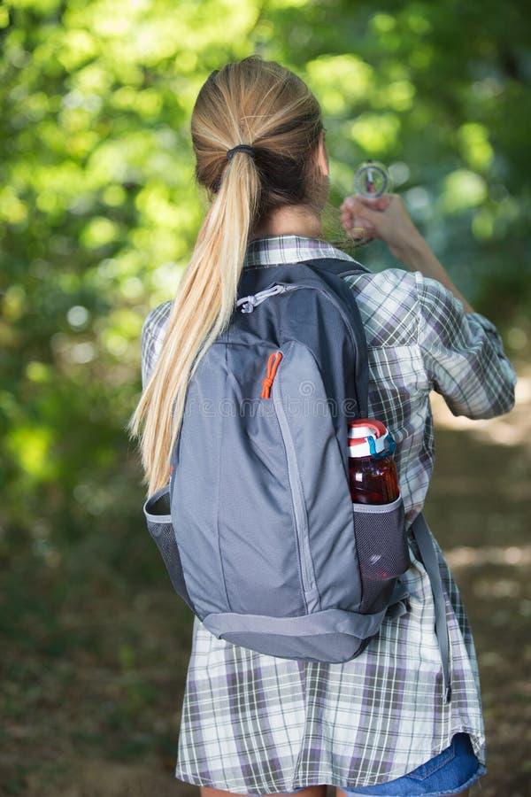 Tylni widoku backpacker mienia żeński kompas fotografia royalty free