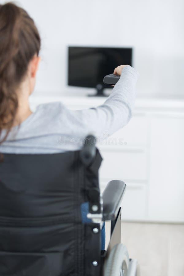 Tylni widoku dama w wózka inwalidzkiego odmieniania kanale telewizyjnym z pilot do tv obrazy royalty free