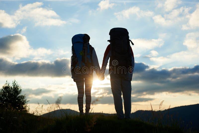Tylni widoku dwa ludzie trzyma ręki z plecakami cieszą się jaskrawego zmierzch w górach zdjęcia stock