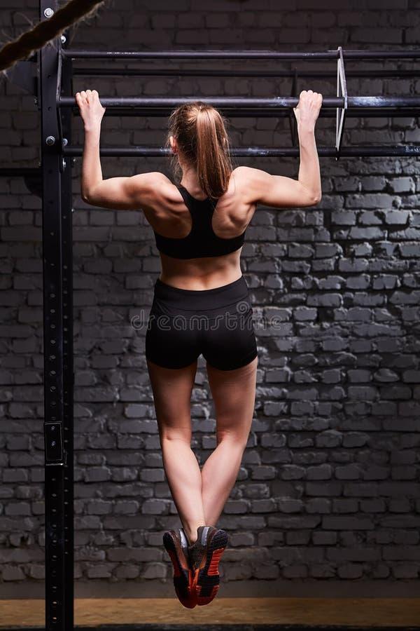 Tylni widoku fotografia młodzi sprawności fizycznej kobiety ciągnienia up na horyzontalnym barze przeciw ściana z cegieł przy krz zdjęcia stock