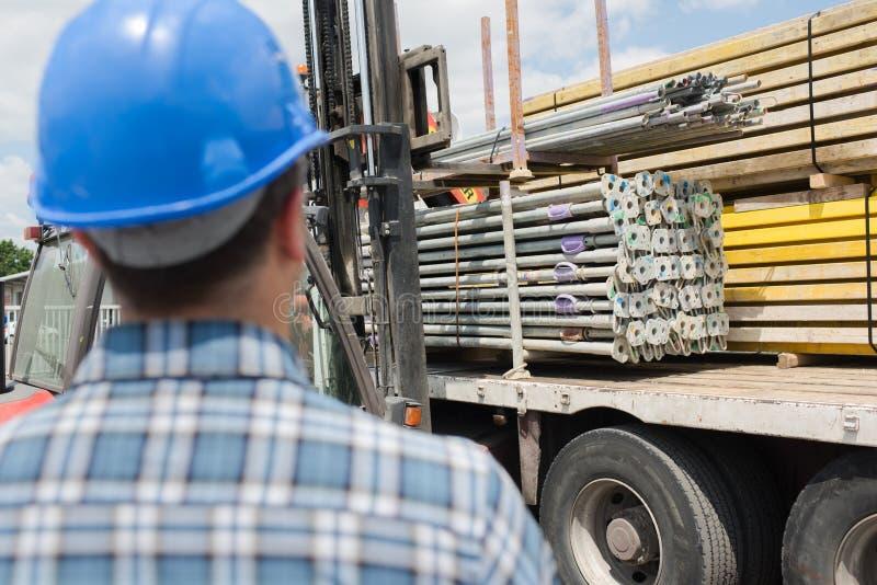 Tylni widoku mężczyzna patrzeje ciężarówka ładunku materiały fotografia royalty free