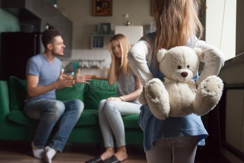 Tylni widoku małej dziewczynki mienia zabawka podczas gdy rodziców walczyć obraz stock