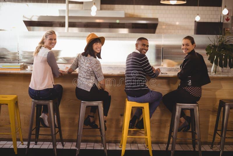 Tylni widoku portret uśmiechnięci młodzi przyjaciele siedzi na stolec przy kontuarem obraz stock