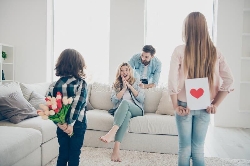 Tylni widoku rodziny dwa fotografie adoptujący dzieci przygotowywający dla mama handmade karcianych świeżych kwiatów 8 maszerują  fotografia stock