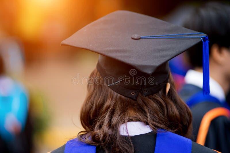 Tylni widoku selekcyjna ostrość uniwersytetów absolwenci tłoczył się w skalowanie ceremonii Absolwent statywowa linia podczas gdy fotografia stock