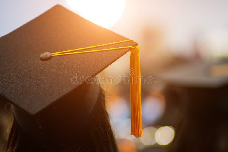 Tylni widoku selekcyjna ostrość uniwersytetów absolwenci tłoczył się w skalowanie ceremonii Absolwent statywowa linia podczas gdy zdjęcia royalty free