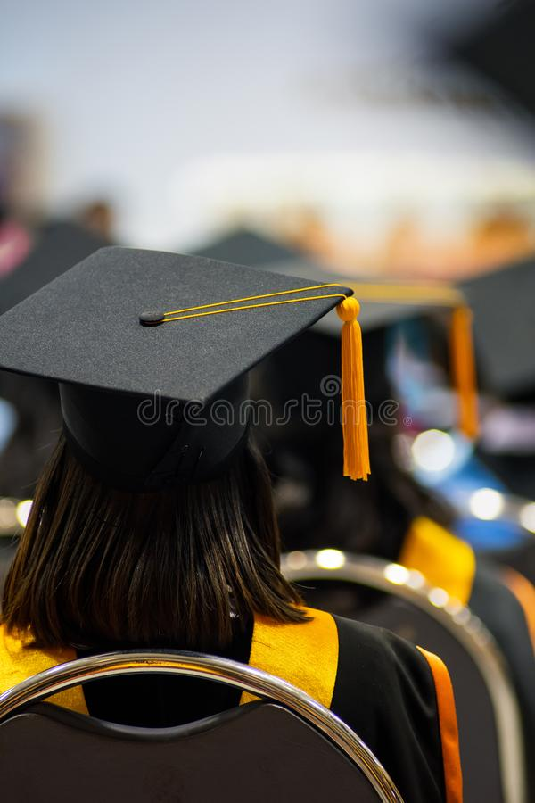 Tylni widoku selekcyjna ostrość uniwersytetów absolwenci tłoczył się w skalowanie ceremonii Absolwent statywowa linia podczas gdy fotografia royalty free