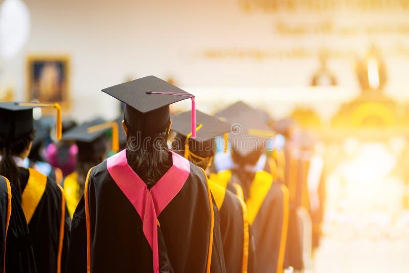 Tylni widoku selekcyjna ostrość uniwersytetów absolwenci tłoczył się w skalowanie ceremonii Absolwent statywowa linia podczas gdy obrazy royalty free
