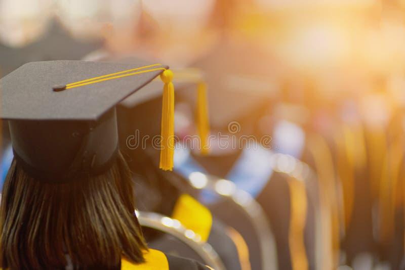 Tylni widoku selekcyjna ostrość uniwersytetów absolwenci tłoczył się w skalowanie ceremonii Absolwent statywowa linia podczas gdy zdjęcia stock