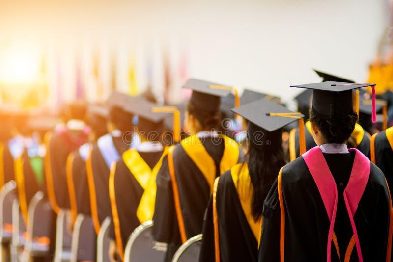 Tylni widoku selekcyjna ostrość uniwersytetów absolwenci tłoczył się w skalowanie ceremonii Absolwent statywowa linia podczas gdy obrazy stock