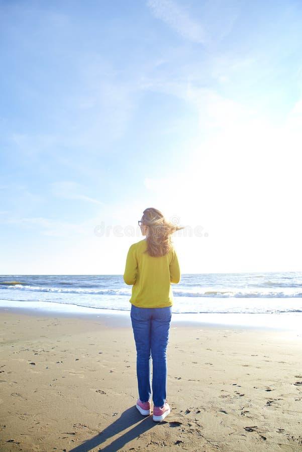 Tylni widoku strzał kobiety pozycja na plaży zdjęcia royalty free