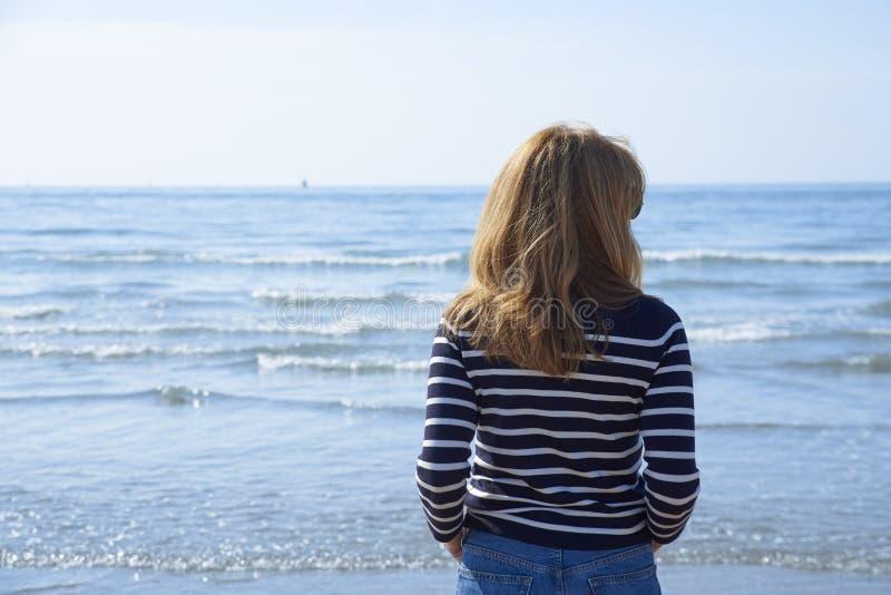 Tylni widoku strzał kobiety pozycja na plaży obraz stock