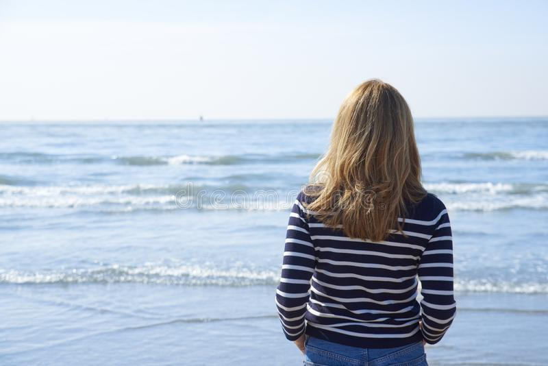 Tylni widoku strzał kobiety pozycja na plaży obraz royalty free