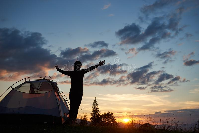 Tylni widoku sylwetka żeńska pozycja z otwartymi rękami zbliża camping w górach zdjęcie stock