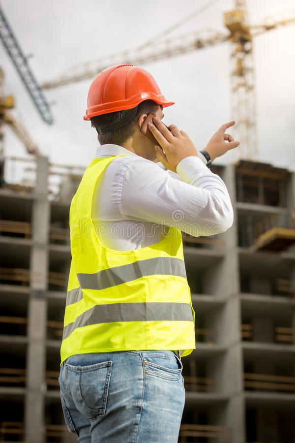 Tylni widoku wizerunek opowiada telefonem na placu budowy i wskazuje przy budować w budowie młody biznesmen fotografia stock