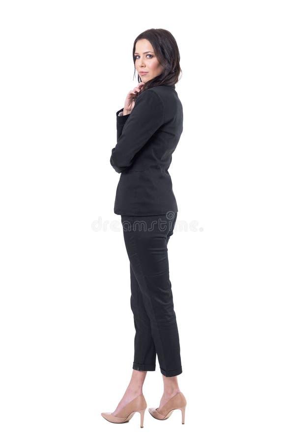 Tylny boczny widok elegancki seksowny biznesowej kobiety kręcenie i patrzeć kamerę w czarnym kostiumu obrazy royalty free