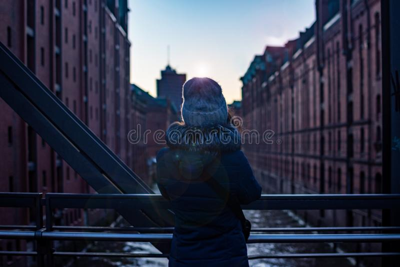 Tylny dziewczyna widok Dziewczyny pozycja na bridżowym dopatrywaniu nowożytny budynek miękki światło i zmierzch Hamburg, Hafencit zdjęcia royalty free