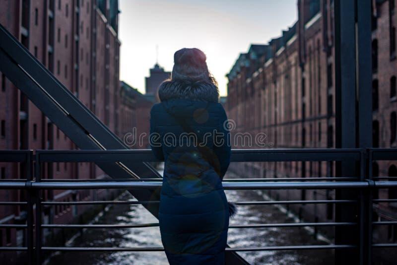 Tylny dziewczyna widok Dziewczyny pozycja na bridżowym dopatrywaniu nowożytny budynek miękki światło i zmierzch Hamburg, Hafencit obrazy stock