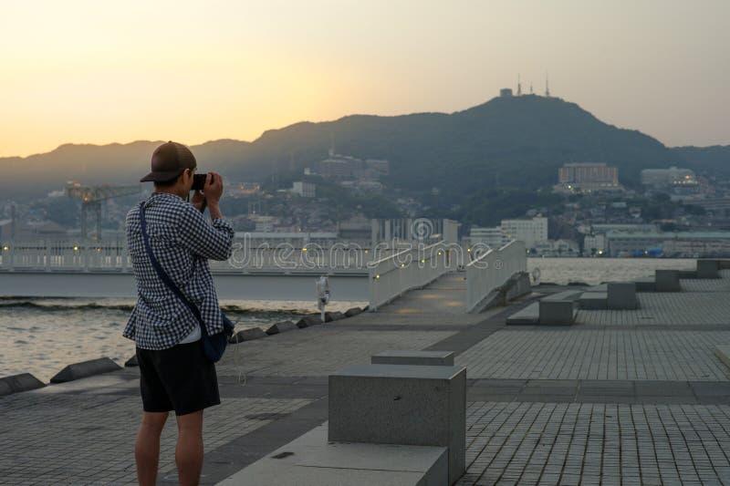 Tylny portret stoi obrazek i bierze Azjatycki mężczyzna krajobraz i pejzaż miejski z górą i zmierzchem w tle zdjęcia stock