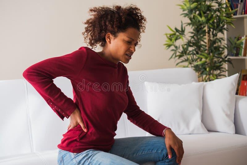 Tylny szyja ból Boleśni kobieta chwyty z ręką jej niski z powrotem zdjęcie stock