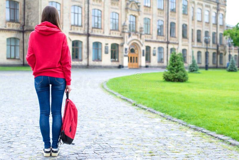 Tylny tyły za pełnej długości bosą wielkościową fotografią poważny ufny skoncentrowany modnisia mienia schoolbag w ręce patrzeje obraz royalty free