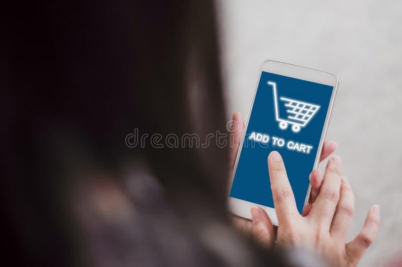 Tylny tylni zakończenie w górę kobiet trzyma smartphones dla online zakupy, pojęcia kupienia produkty od sklepów z dogodnością, i obrazy stock