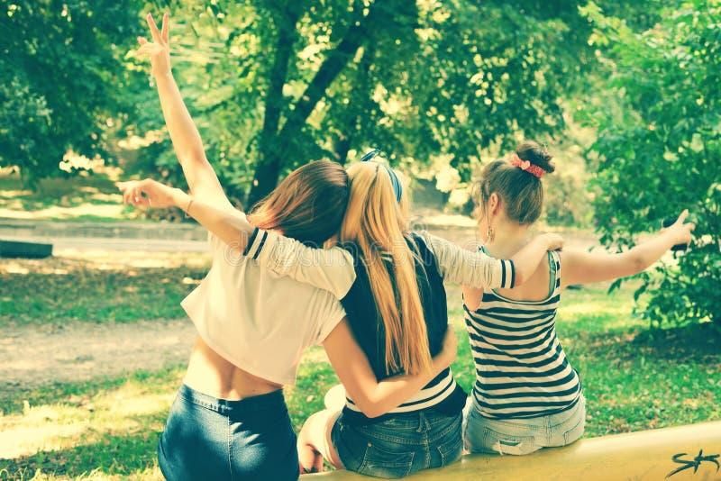 Tylny widok śliczne dziewczyny sadzać na żółtej ławce i relaksować fotografia stock