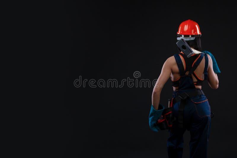 Tylny widok żeński pracownik trzyma hełm na czarnym tle i młot zdjęcie royalty free