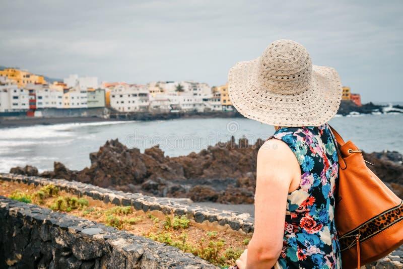 Tylny widok żeński turysta z plecakiem podziwia widok obrazy stock