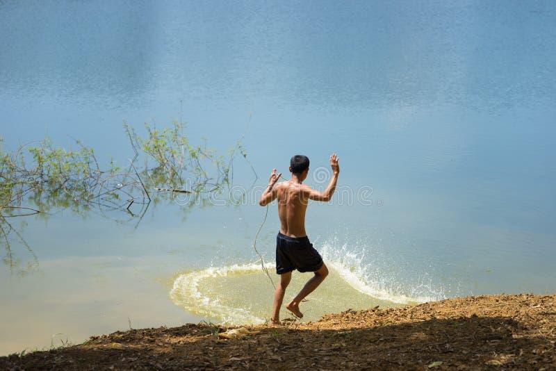 Tylny widok Azjatycka rybaka miotania ryba sieć chwyt ryba na jeziorze fotografia stock