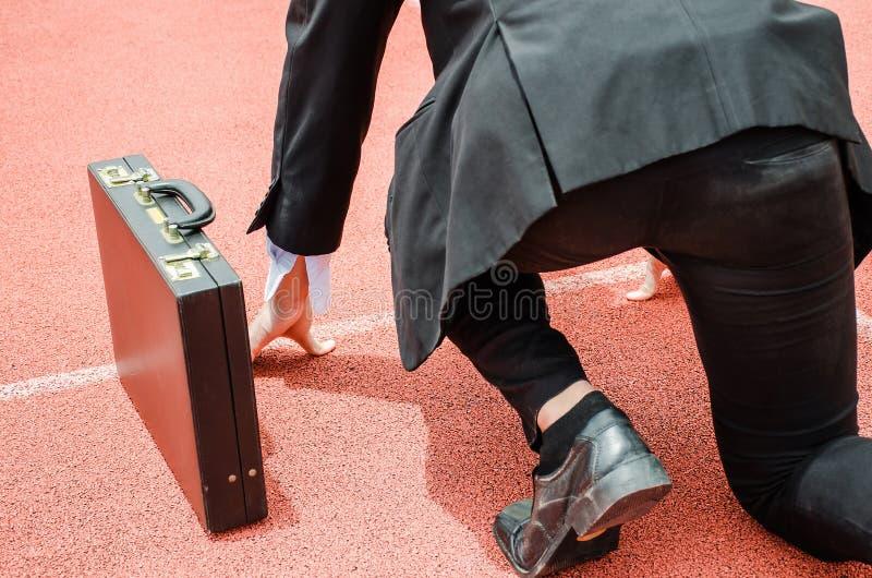 Tylny widok azjatykci biznesowy mężczyzna gotowy biegać na pas ruchu ślad obrazy stock