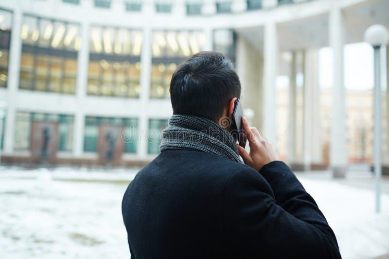 Tylny widok biznesmena mówienie telefonem w mieście obrazy stock