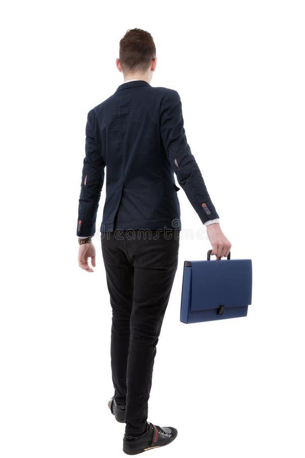 Tylny widok biznesowy mężczyzna trzyma chodzącego forw i teczkę zdjęcia stock