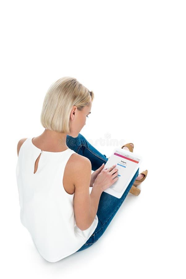 Tylny widok blondynki kobieta używa cyfrową pastylkę z instagram app, odizolowywający na bielu zdjęcia stock