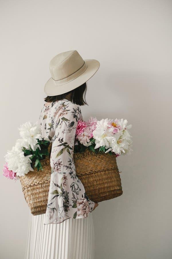 Tylny widok boho dziewczyny mienia różowe i białe peonie w nieociosanym koszu Elegancka modniś kobieta w kapeluszowej i artystycz obraz stock