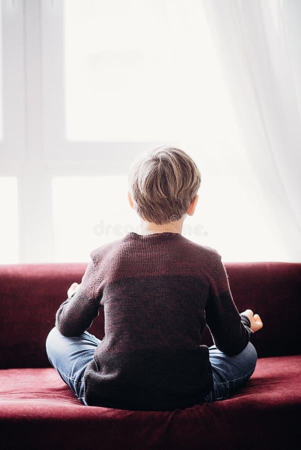 Tylny widok chłopiec obsiadanie na kanapie w lotosowej pozie zdjęcie stock
