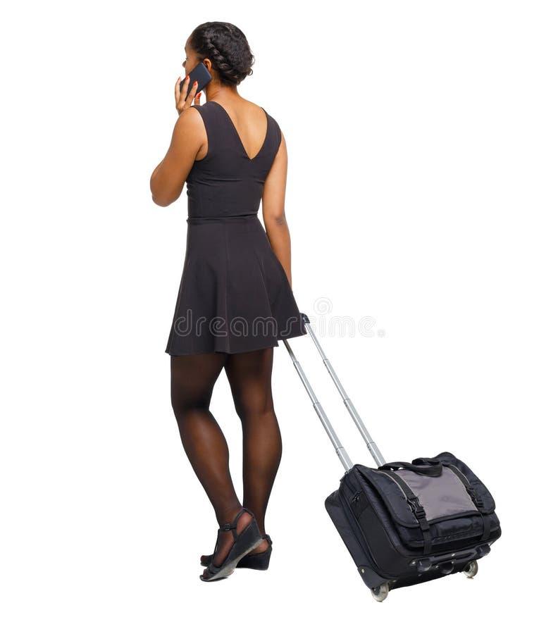 Tylny widok czarny afroameryka?ski odprowadzenie z walizk? zdjęcie stock