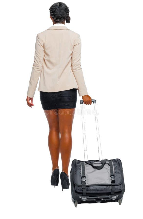Tylny widok czarny afroamerykanin w formalnym ubioru odprowadzeniu z walizk? zdjęcia stock