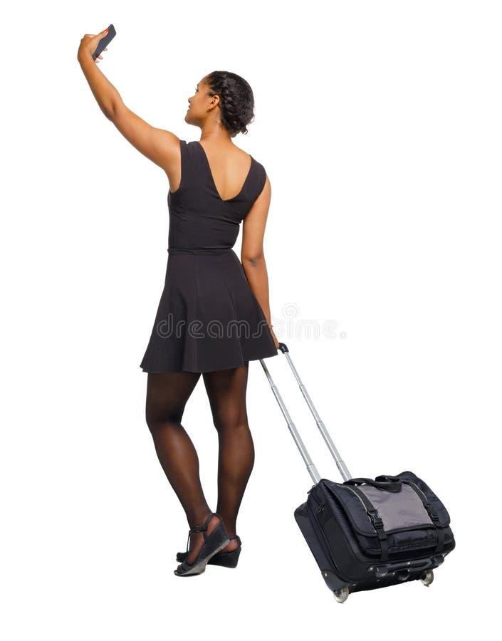 Tylny widok czarny afroamerykanin z walizką z mądrze obraz stock