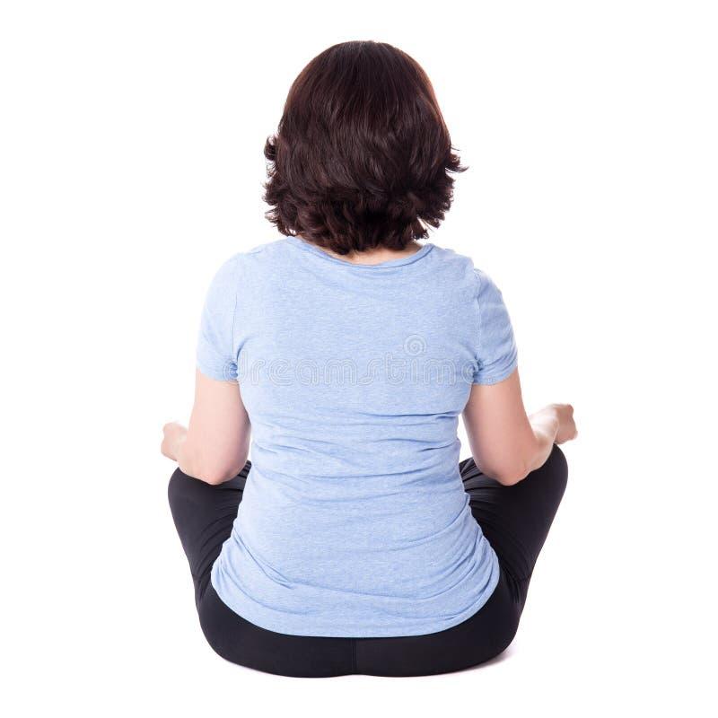 Tylny widok dojrzały kobiety obsiadanie w joga pozie odizolowywającej na bielu obrazy stock