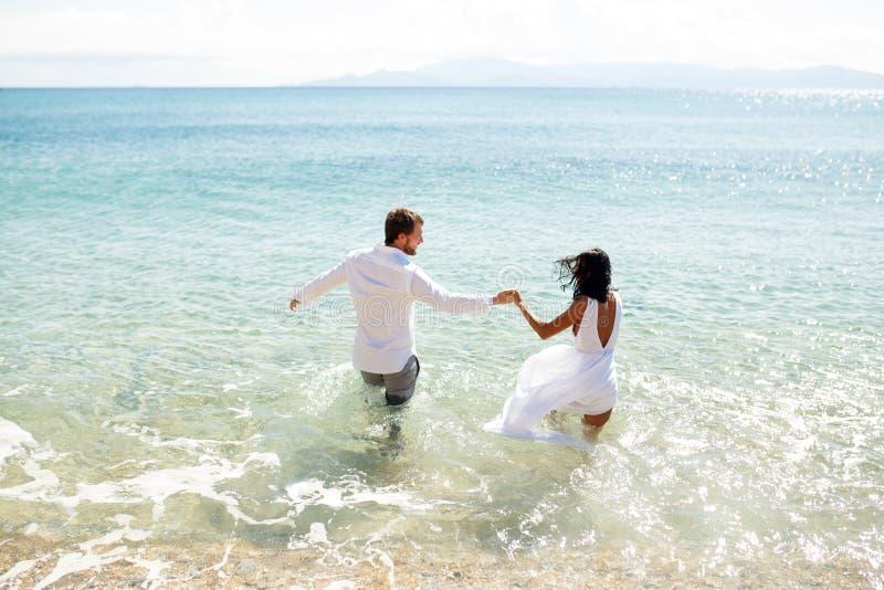 Tylny widok dwa młoda osoba nowożeńcy wchodzić do w wodzie w odzieży, cieszy się w wakacje, lato czas, morze w Grecja obraz royalty free