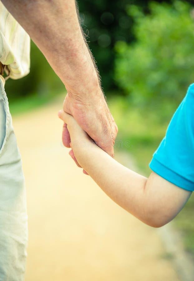 Tylny widok dziecka i starszego mężczyzna mienia ręka obrazy stock