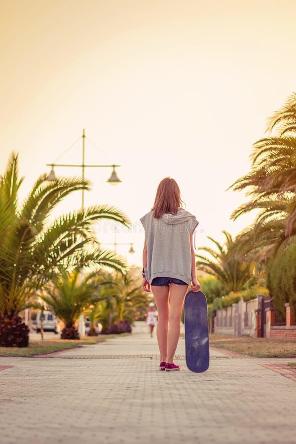 Tylny widok dziewczyna z deskorolka outdoors dalej fotografia stock