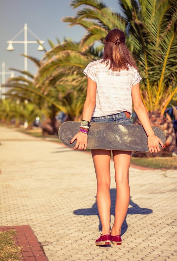 Tylny widok dziewczyna z deskorolka outdoors dalej fotografia royalty free